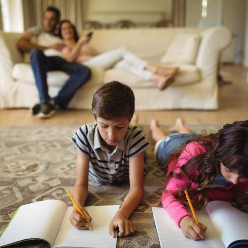 Kids doing homework while lying on rug